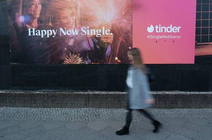 Una mujer pasea delante de un anuncio de Tinder en febrero en Berlin,