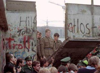 Guardas fronterizos de la República Democrática Alemana observan el derribo del muro de Berlín, en 1989.