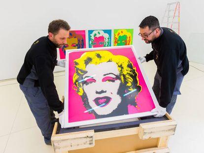 Operarios colocan las pinturas de Marilyn Monroe.