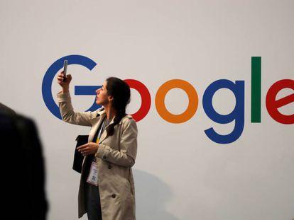 Una usuaria consulta su móvil junto al logotipo de Google.