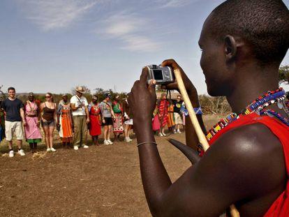 Un joven masai toma una foto a un grupo de turistas.