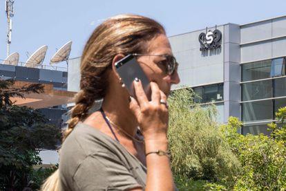 Una mujer usa su teléfono móvil frente al edificio de la empresa israelí NSO Group, desarrolladora del 'software' espía Pegasus, en Tel Aviv.