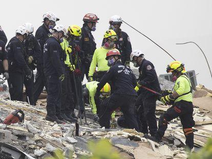Miembros de la unidad de rescate de Florida buscan desaparecidos entre los escombros.