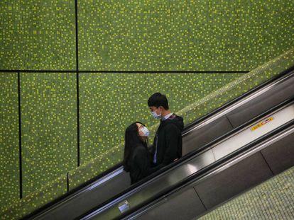 Una pareja vive su amor en tiempos ce coronovirus en un centro comercial de Hong Kong.