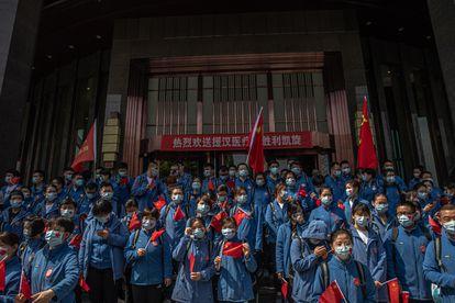 Trabajadores médicos chinos de la provincia de Shandong participan en una ceremonia antes de abandonar Wuhan.