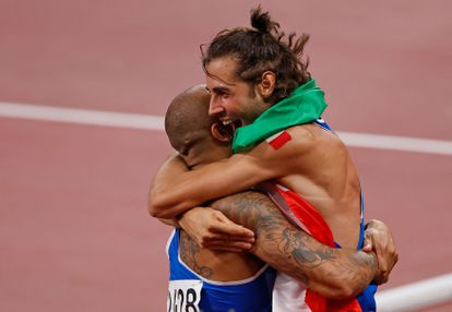 Jacobs hugs himself with the day's other Italian gold medalist, jumper Gianmarco Tamberi, moments after winning the 100m final.