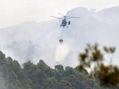 Un helicóptero lanza agua sobre el incendio de Yeste (Albacete).