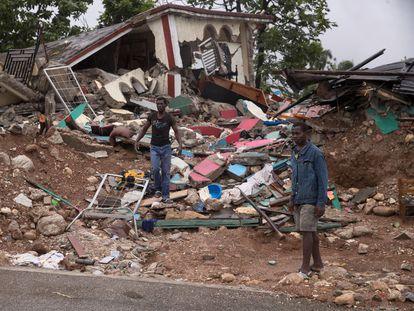 Hombres caminan junto a una casa destruida, mientras cae la lluvia que deja el paso de la tormenta 'Grace', este martes en Camp Perrin (Haití).