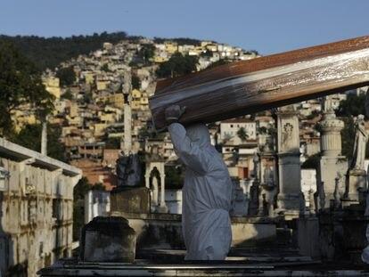 Dos personas cargan el ataúd de una persona fallecida por coronavirus en un cementerio de Rio de Janeiro, Brasil.