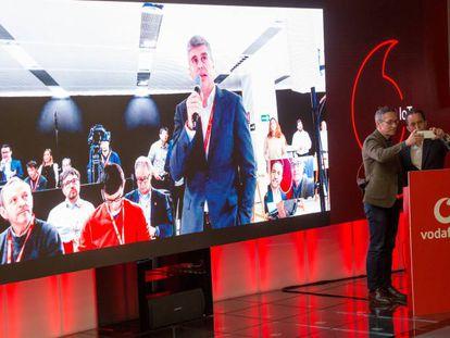 Videollamada 5G entre Albert Buxadé, de Vodafone, en la pantalla, y el secretario de Estado para la Sociedad de la Información, José María Lasalle (en el atril)