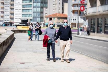 Varias personas pasean por el Paseo Marítimo de Sanxenxo, en Pontevedra, Galicia (España).