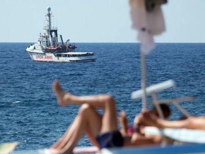 El barco de rescate 'Open Arms', ante las costas de Lampedusa (Italia) mientras unos turistas toman el sol en la isla.