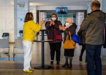 Personas con mascarillas protectoras y usando jabón desinfectante en la entrada del hospital de Cremona.
