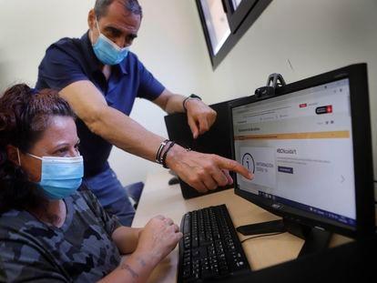 Un hombre ayuda a una mujer a realizar unos trámites 'online'.