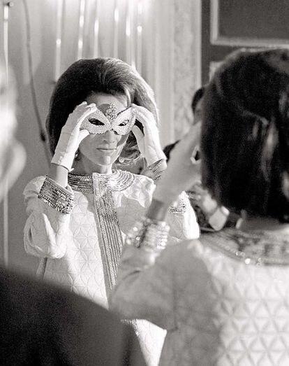 La prrincesa Lee Radizwell, hermana de Jackie Kennedy, se ajusta la máscara después de llegar al baile.