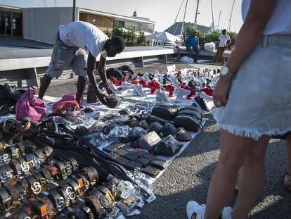 Un mantero vende sus productos en el muelle de la Barceloneta.