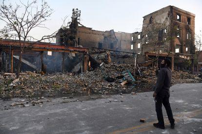 Un hombre toma fotografías de los edificios quemados en Minneapolis.