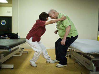 Marta Fernández, fisioterapeuta, ayuda a Javier Herreros a realizar unos ejercicios en el Centro Estatal de Atención al Daño Cerebral, en Madrid.