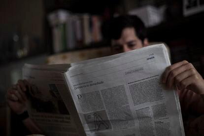 Un lector, con un ejemplar del diario EL PAÍS.
