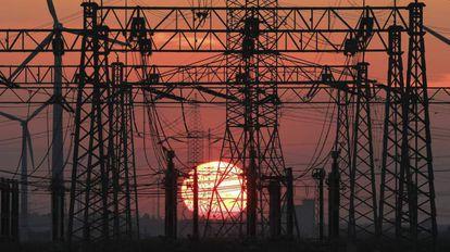 Puesta de sol junto a un tendido eléctrico y unos molinos de viento (izq).