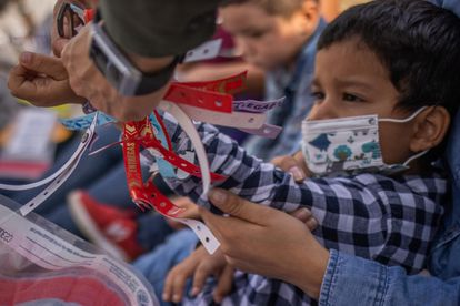 Un agente fronterizo de Texas le quita un brazalete de estatus migratorio a Santiago, quien viajó con su madre desde Honduras para solicitar asilo.