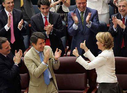 Los diputados populares aplauden a Esperanza Aguirre, que hace un gesto de triunfo a su vicepresidente, Ignacio González.