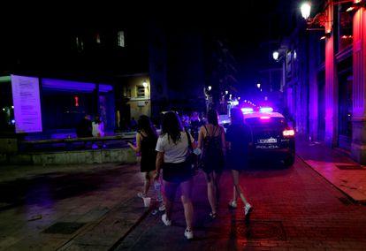 Varios jóvenes turistas pasan ante un coche de policía el 13 de julio en la calle Caballeros del barrio de El Carmen de Valencia.