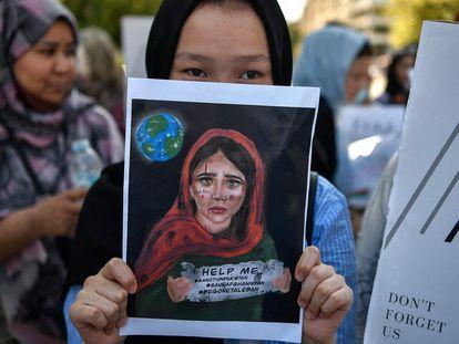 Una joven sostiene una pancarta durante una manifestación de miembros de la comunidad afgana frente a la embajada de Estados Unidos en Atenas.