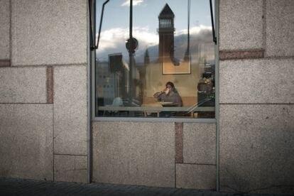 Una joven desayuna en el interior de un bar en plaza España de Barcelona.
