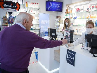 Un cliente mantiene la distancia de seguridad mientras es atendido en una farmacia del centro de Madrid.