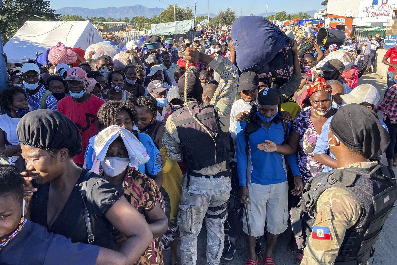 Varios agentes amenazan con sus látigos a la multitud agolpada en el puente del río Massacre, en la frontera norte de Ouanaminthe, a la espera de cruzar al mercado binacional del lado dominicano. Pincha en la imagen para ver la fotogalería.