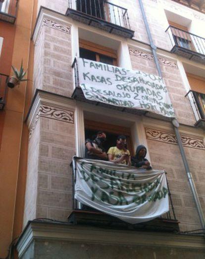 Varios de los okupas del edificio de la calle Tres Peces en uno de los balcones, donde han colocado carteles.