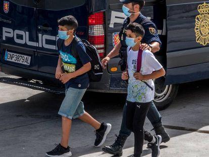 Un policía nacional acompaña a dos menores, el pasado 20 de mayo en Ceuta.