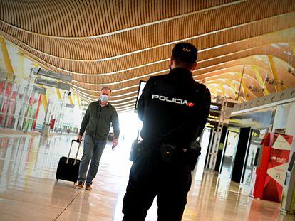 Un policía controla el acceso a la T-4 del Aeropuerto Adolfo Suárez Madrid-Barajas, el viernes 10 de octubre, para vigilar el cumplimiento de las restricciones a la movilidad impuestas por el estado de alarma en Madrid que decretó el Gobierno.