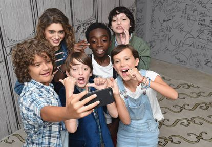 Los más jóvenes del reparto de Stranger Things (Gaten Matarazzo, Natalia Dyer, Noah Schnapp, Caleb McLaughlin, Finn Wolfhard y Millie Bobby Brown) y un móvil.