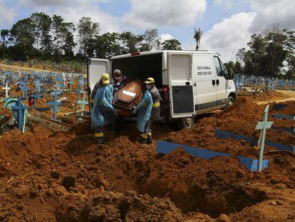 Trabajadores de un cementerio llevan los restos de un hombre que murió a causa del coronavirus, para enterrarlos en el cementerio Nossa Senhora Aparecida en Manaus, estado de Amazonas, Brasil, el pasado 6 de enero.