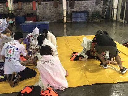 Personal del servicio de rescate atiende este jueves en el puerto de Phuket (Tailandia) a varios pasajeros rescatados de un barco a la deriva.