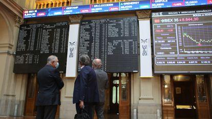Tres hombres observan los valores económicos de la Bolsa de Madrid, en mayo.