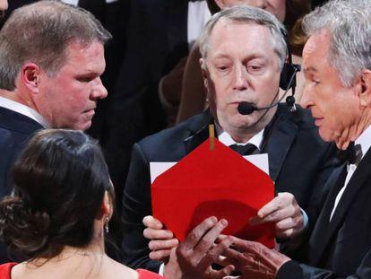 FOTO: Brian Cullinan, a la izquierda y con cara seria, auditor de PwC, habla con Warren Beatty en el escenario. / VÍDEO: Entrega equivocada del Oscar a la mejor película