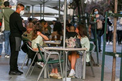 Un camarero atiende a unas clientas en una terraza de Madrid a principios de abril.
