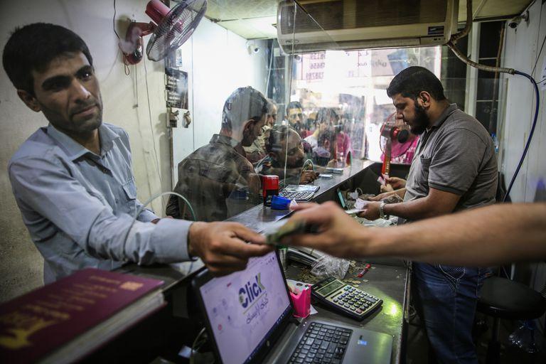 Unos sirios cambian la moneda local por liras turcas o dólares en una casa de cambio informal en la insurrecta provincia de Idlib.