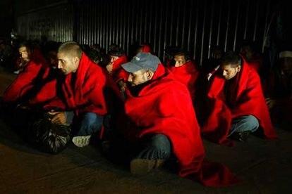 Los inmigrantes interceptados el viernes en el Estrecho se calientan con mantas de la Cruz Roja.