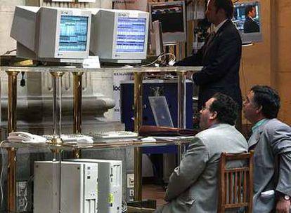 Dos inversores observan pantallas con las cotizaciones en el patio de operaciones de la Bolsa de Madrid.