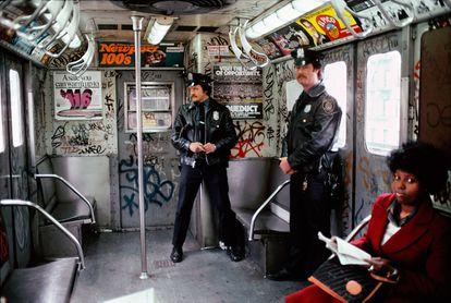 Dos agentes de policía y una pasajera viajando en 1981 en un vagón del metro de Nueva York cubierto de pintadas.