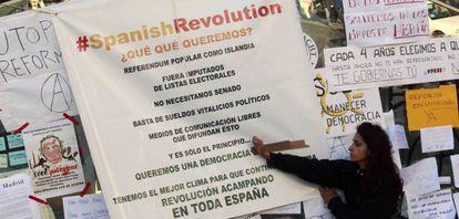 Una joven pega un cartel con las reivindicaciones en la Puerta del Sol.