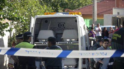 Los agentes, junto al coche con los féretros de los cuatro fallecidos en el incendio de una vivienda en Jaén este sábado.