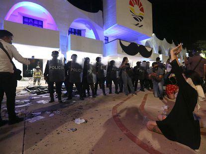 Mujeres manifestantes frente a la policía en el centro de Cancún.