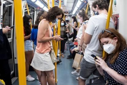Grupo de personas consultando sus teléfonos móviles en un vagón del metro de Madrid.