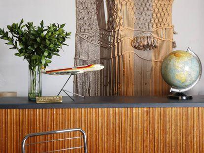 Ante un tapiz y sobre el mostrador de Almacén Alquián Hóptimo, una miniatura de un avión Iberia y un globo terráqueo.  