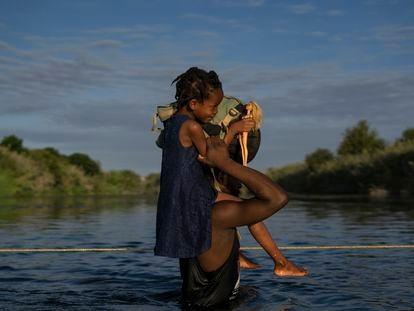 Un hombre haitiano con su hija a hombros cruza el Río Bravo entre Del Río (Texas) y Ciudad Acuña (México), este 22 de septiembre de 2021.